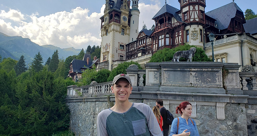 IE alum Brian Fleming poses outside of a castle in Romania