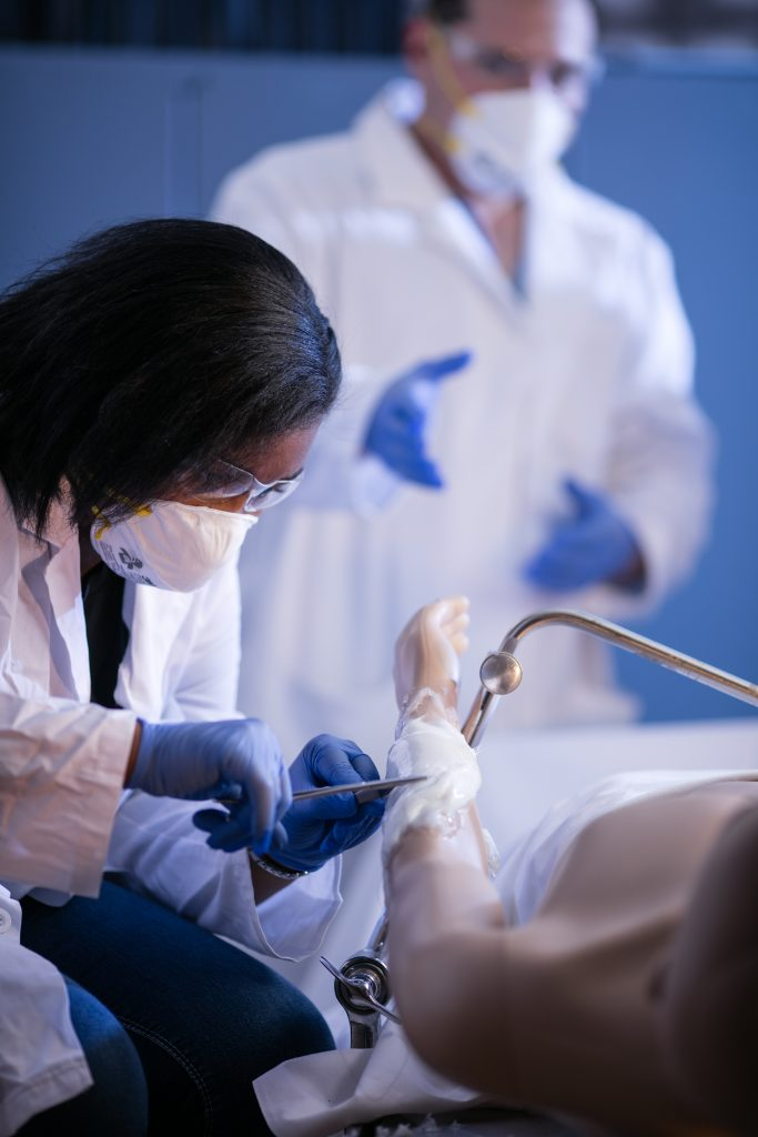 A student performs a surgical operation on a mannequin. The student is wearing safety glasses, a face mask, rubber gloves and a white lab coat. A professor can be seen in the background guiding her through the process.
