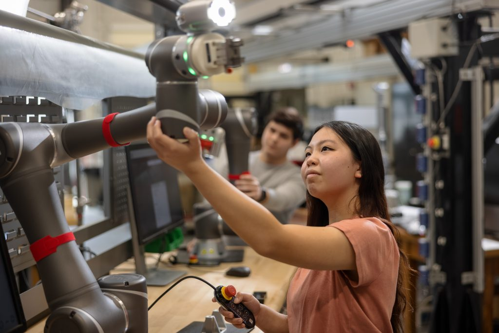"""A student works with a co-bot, which is a combination of the words """"collaborative"""" and """"robot."""" The idea is that the robot is not fully autonomous and requires the operator to work with it."""